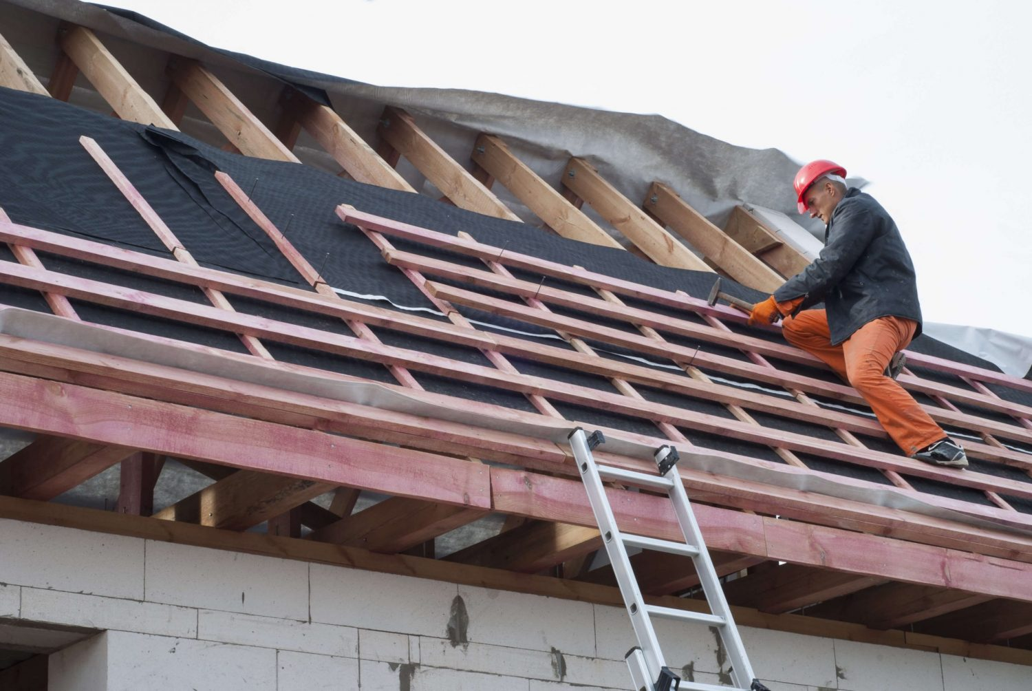Full roof restoration services. Roofer working on wood roof deck.